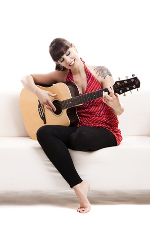 woman guitar: Beautiful woman sitting on the sofa and playing guitar, isolated on white
