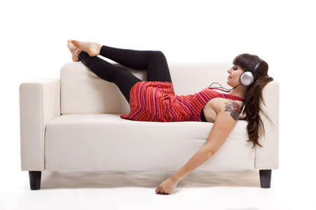 woman listening to music: Beautiful woman lying on the sofa and listen music with headphones, isolated on white