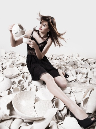 shards: Fashion photoshoot with  a beautifulyoung woman holding pieces of porcelain Stock Photo