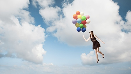 Fashion photoshoot with  a beautiful young woman flying with balloons over the sky photo