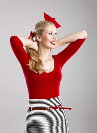 Beautiful fashion woman in red posing with a paper hat on the head photo
