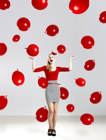 Beautiful fashion woman in red posing with red ballons photo