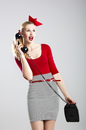 Beautiful fashion woman with a astonished expresion and holding a  vintage phone photo
