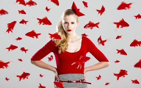 Beautiful fashion woman with red fishes around her photo