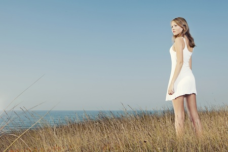 sea grass: Beautiful young woman in a white dress relaxing in a meadow close to the sea
