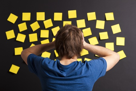 overwork: Young student with stress and looking to a board full of yellow notes