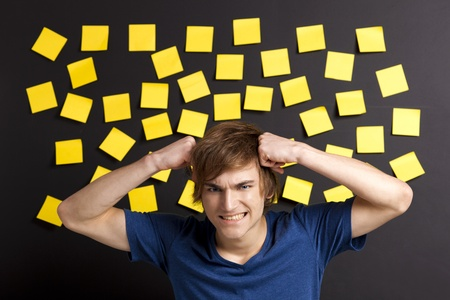 сooking: Stressed young student in front of a board full of yellow notes Stock Photo