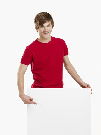 Portrait of a happy young man showing something on a blank white card photo