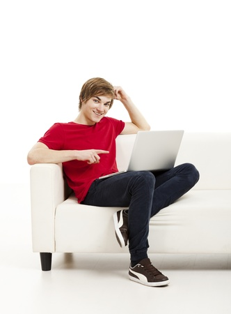red couch: Handsome young man at home sitting on the couch and working on the laptop Stock Photo