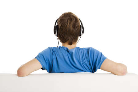 escuchar: Joven sentado en el sof? y escuchar m?sica, aislados en blanco Foto de archivo