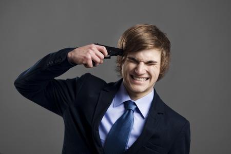 Stressed businessman giving a gunshot on his own head photo