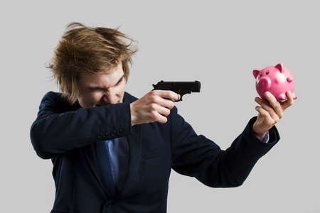 Businessman holding and pointing a gun to a piggy bank photo