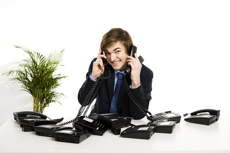 Businessman sitting with a bunch telephones on his front photo