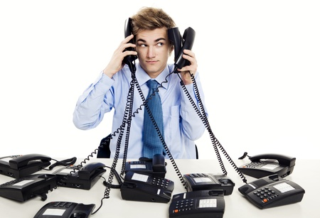 telephony: Young man in the office and answering several phones at the same time