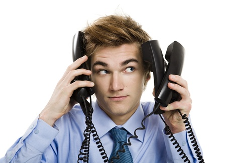 Young man in the office and answering several phones at the same time Stock Photo - 21717784