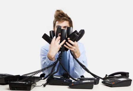 helpline: young man in the office and answering several phones at the same time