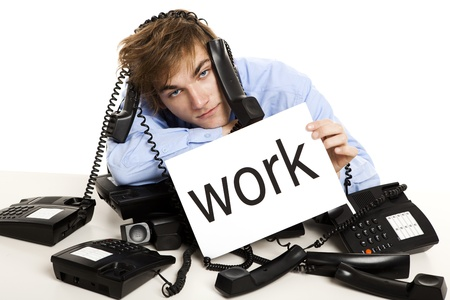 answering phone: Exhausted man full of work, sitting with a bunch of phones over him and holding a cardboard with the word Work.