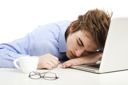 Exhausted businessman in the office sleeping over the laptop photo