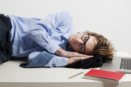 unemployed dismissed: Young man in the office and sleeping over is desk Stock Photo