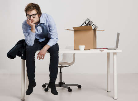 unemployed dismissed: Young man sitting on the desk after being fired