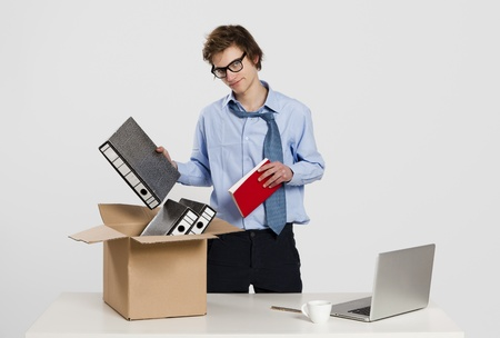 Young man in the office packing up after being fired photo