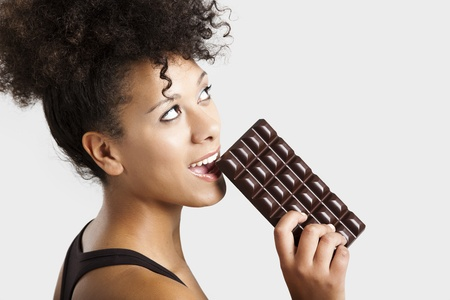 Beautiful african woman holding and eating a huge dark chocolate bar photo