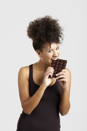 american content: Beautiful african woman holding and eating a huge dark chocolate bar