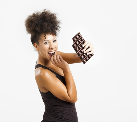 chocolate bars: Beautiful african woman holding and eating a huge dark chocolate bar