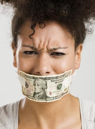 boca cerrada: African American mujer tap?ndose la boca con un billete de d?lar, concepto ideal para la crisis global
