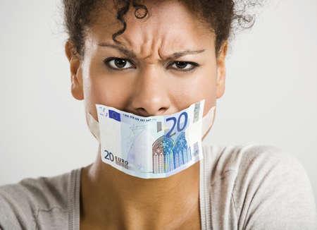 boca cerrada: Mujer africana que cubre su boca con un billete en euros, gran concepto para la crisis global