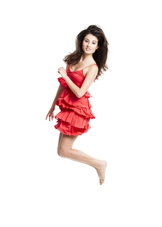 Beautiful woman with a red dress dancing and jumping, isolated on white photo