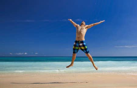 hombre flaco: Hombre atl?tico joven disfrutando del verano, saltando en una playa tropical