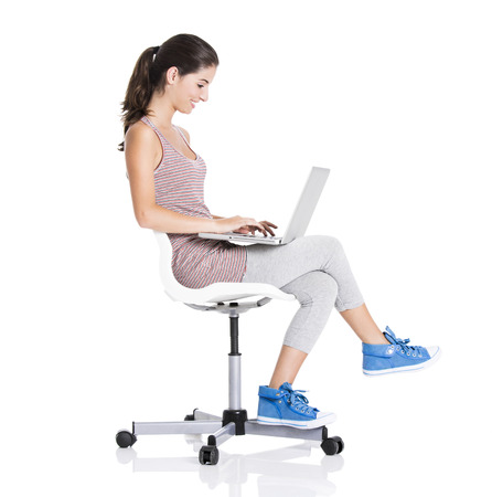 Beautiful student sitting in a chair with a laptop, isolated over a white background photo