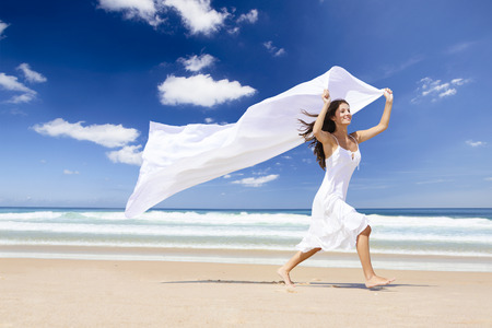Beautiful girl in the beach running and holding a white piece of fabric photo