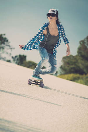 Young woman down the road with a skateboard photo