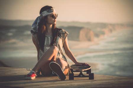 sonnenbrille: Schöne junge Frau auf einem Skateboard sitzend Lizenzfreie Bilder