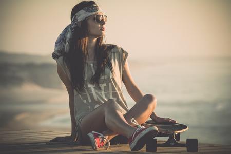 skateboarding: Beautiful young woman sitting over a skateboard