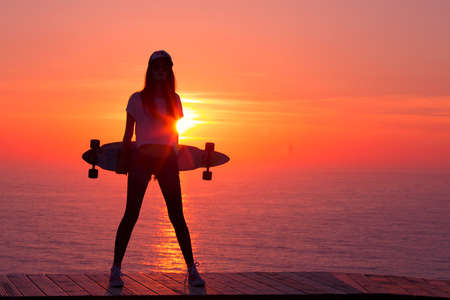 skateboarding: Beautiful and fashion young woman posing at teh sunset with a skateboard Stock Photo