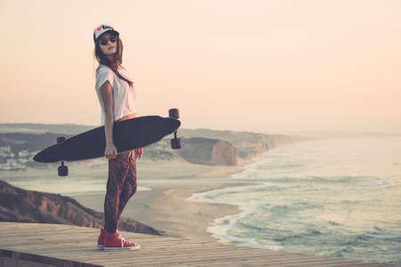 patinar: Bello y moda joven posando con una tabla de skate Foto de archivo