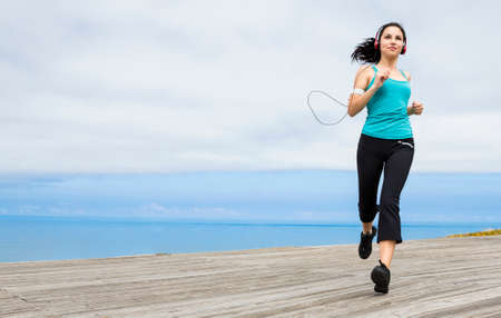 Beautiful young woman jogging on a boardwalk and listen music Stock Photo