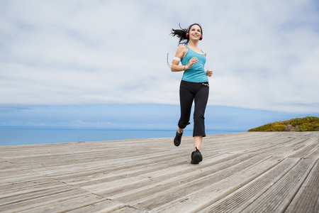 Beautiful young woman jogging on a boardwalk and listen music photo