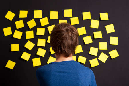 Young student looking to a board full of yellow notes photo