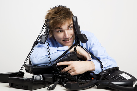 Young man sitting with a bunch of phones over him photo