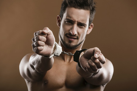 handcufs: Handsome young man arrested with handcufs on his hands