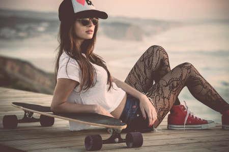 fashion: Joven y bella mujer y la moda posando con una tabla de skate Foto de archivo