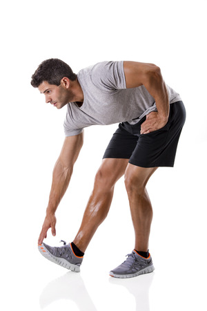 Athletic man doing some warming exercises, isolated over a white background photo