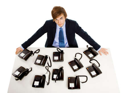 Young man in the office with a bunch telephones on his front photo