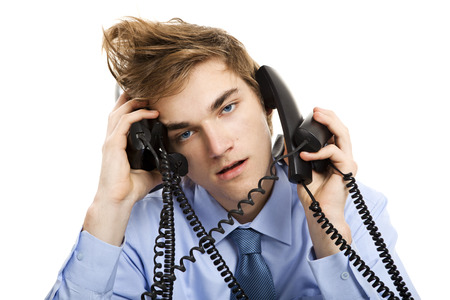 answering call: Young man sitting in the office and answering several phones at the same time Stock Photo