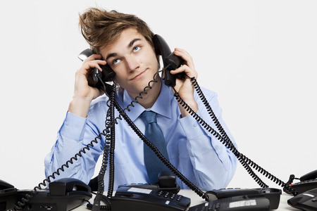 telephony: Young man sitting in the office and answering several phones at the same time Stock Photo