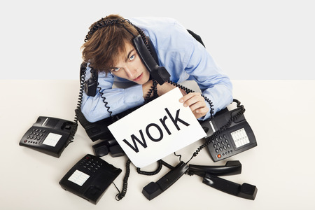 Exhausted man full of work, sitting with a bunch of phones over him and holding a cardboard with the word Work. photo
